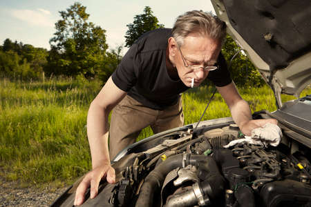 Aging man trying to fix broken car engine on lonely way
