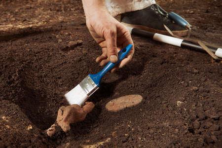 Arqueólogo en ubicación tropical durante el hallazgo de una rara estatua de mujer votiva