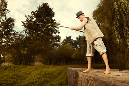Man in bowler hat and fishing rod trying to catch fish Reklamní fotografie