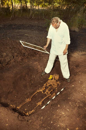 Archaeologist on outdoor location exploring ancient grave