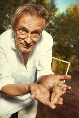 Archaeologist on outdoor location showing his finds