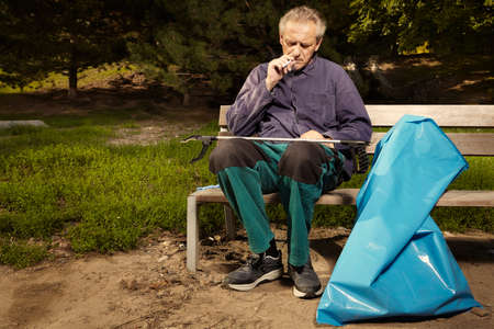 Man in public service relaxing after cleaning up trash in city park