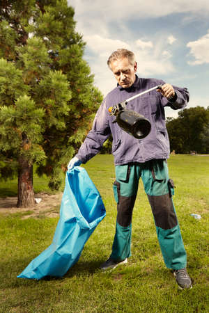 Man in public service cleaning up trash in city park