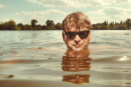 Funny man in sunglasses swimming in lake on sunny daytime