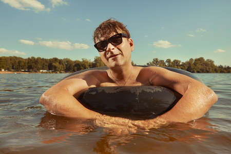 Funny man in sunglasses swimming in lake on inner tube