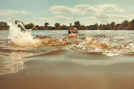 Funny man in water swimming in lake on daytime