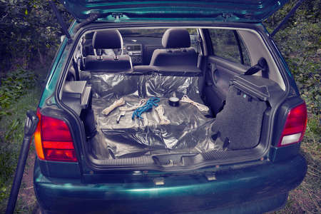 Car trunk of killers vehicle prepared with plastic foil, ropes, tapes and weapons