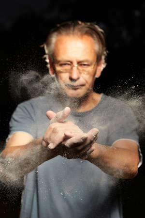 Homme frappant des mains pour enlever la poussière et la saleté de la peau