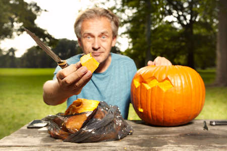 Older man carving helloween pumpkin for upcoming holiday event