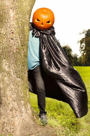 Older man in hooded cloak haunts in city park