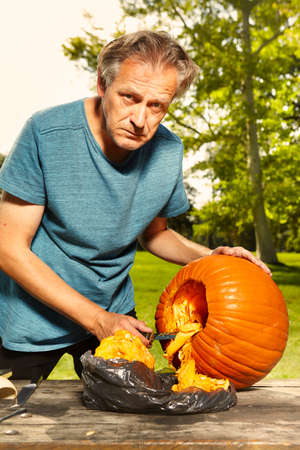 Older man carving helloween pumpkin for upcoming holiday event Stock Photo