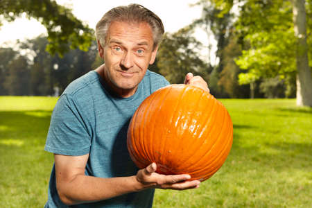 Older man cleaning and preparing helloween pumpkin for carving Stock Photo