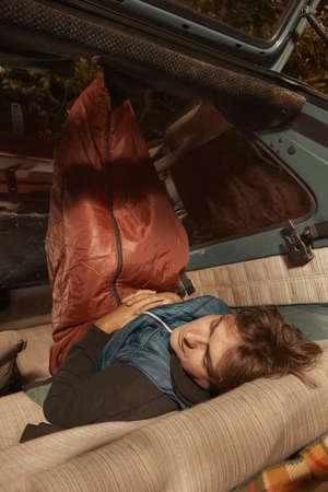 旅行の男は彼の車の中で夜を過ごすためにルートの近くに停止します