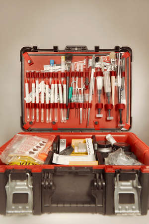 Suitcase of criminologist technician with many tools of evidence collecting