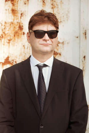 Man in suit and glasses posing by the rusty wall Archivio Fotografico - 133517159