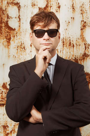 Man in suit and glasses posing by the rusty wall Archivio Fotografico - 133517161