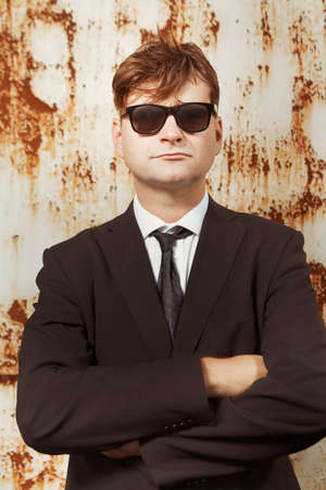 Man in suit and glasses posing by the rusty wall