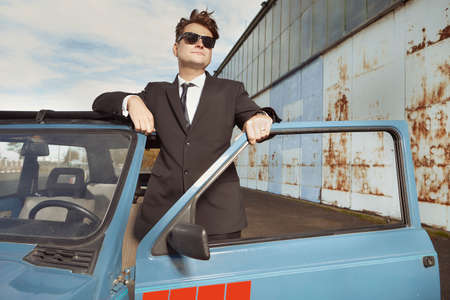 Man in black suit posing with his lovely retro car