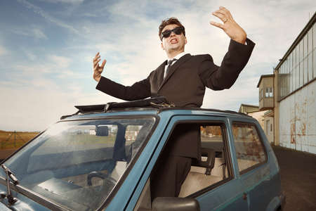 Man in black suit gesturing on his lovely retro car