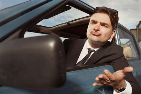 Man in black suit driving his lovely retro car