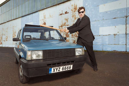 Angry man in black suit destroying his lovely retro car