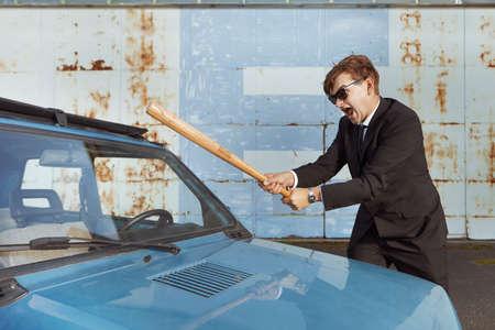 Hombre enojado en traje negro destruyendo su encantador coche retro