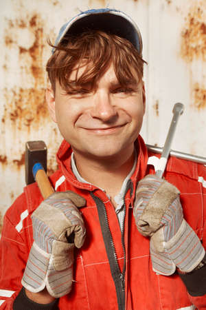 Cute man in red overall posing with tools for portrait