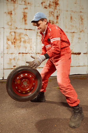 Cute man in red overall tunning his lovely retro car Stock Photo