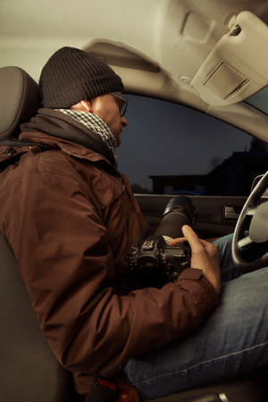 Photographer inside car waiting in the evening time for person to catch