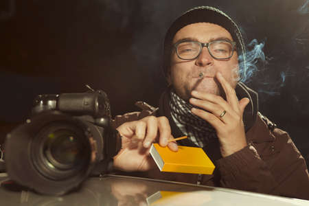 Photographer smoking cigarette waiting in the evening time for person to catch