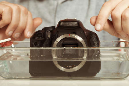 Crazy technician cleaning digital camera bad way in water