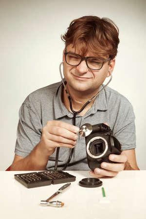 Crazy technician repairing digital camerabody bad way like a doctor Stok Fotoğraf