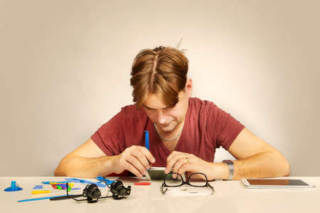 Man working on repairing of broken smartphone with zoom lens Stok Fotoğraf