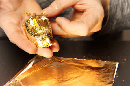 Artwork of gilding - covering an object with plate metal gold Stok Fotoğraf