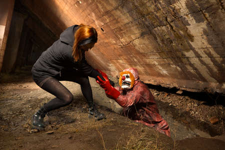 Scary clown man in nightmare style attacking young woman