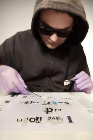 Criminal in hooded shirt preparing ransom letter from newspaper Imagens
