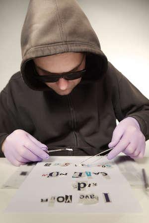 Criminal in hooded shirt preparing ransom letter from newspaper