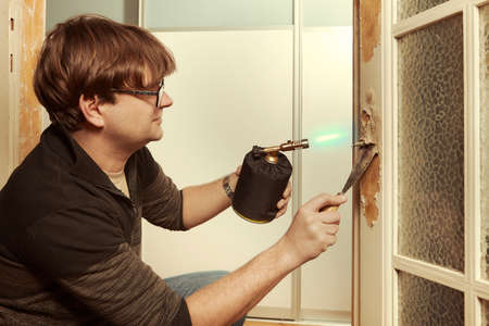 Man at home removing havy layer of old paint from door with burner