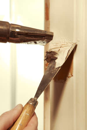 Man at home removing havy layer of old paint from door Standard-Bild