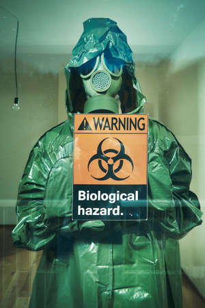 Ugly man in empty apartment dressed to protective suit and mask