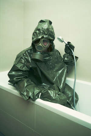 Ugly man in bathroom dressed to protective suit and mask showering Foto de archivo