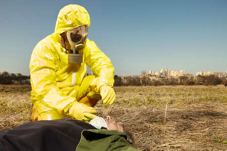 Man in virus protective suit taking sample from body found outdoor for analysis