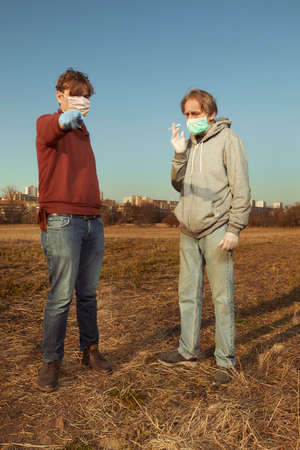 Two men in face mask relaxing and enjoying sunny day on city meadow