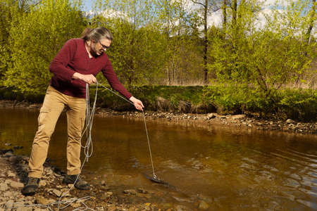 Man exploring river water by magnet on rope Stock Photo