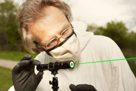 Criminologist technician in protective suit and mask working with ballistics laser Foto de archivo