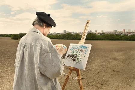 Älterer Mann malt Kunstwerke auf Leinwand im sonnigen Tagesfeld