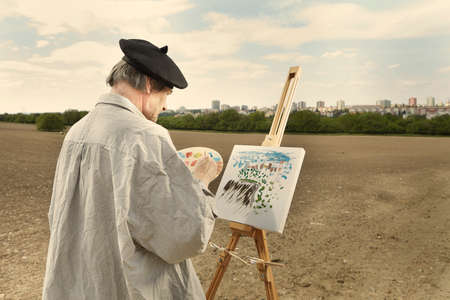 Older man painting artwork on canvas in sunny day field