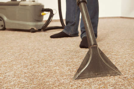 Caucasian man cleaning deeply carpet with wet cleaning machine