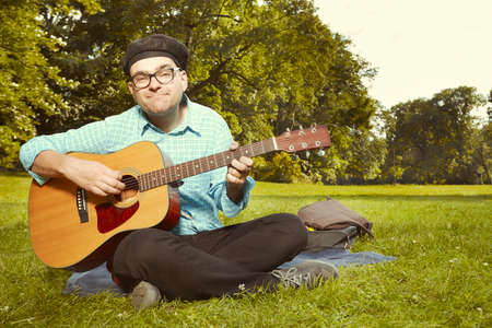 Funny man on city park summer meadow enjoying day with guitar Stock Photo
