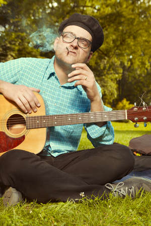 Funny man on city park summer meadow enjoying day with guitar Archivio Fotografico